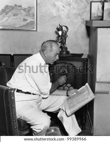 Man listening to radio and reading newspaper