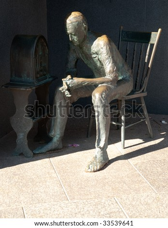 man listening to radio statue