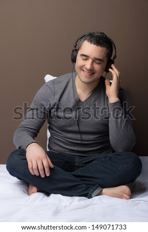 Man listening to the music. Relaxed middle-aged man listening to the music while sitting on the sofa