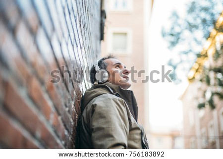 Man listens to music with headphones and smart phone. It is in an area of red brick wall. #756183892