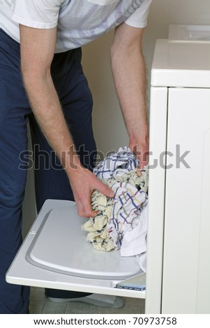 Man loading clothes into dryer dressed in casual clothes.