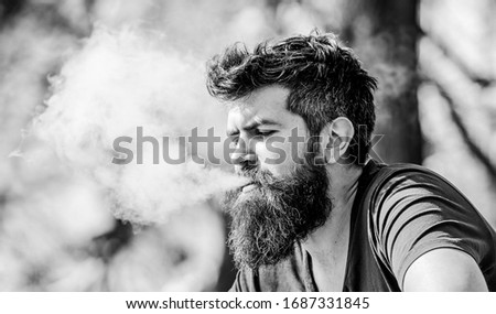 Man long beard relaxed with smoking habit. Man with beard breathe out smoke. Clouds of flavored smoke. Stress relief concept. Bearded man smoking vape. Smoking electronic cigarette. Smoking device.