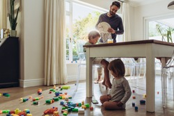 Man looking after his kids while doing the household works. Kid playing with toys sitting on floor with his father doing daily household chores.