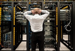 Man looking astonished in a network data center.