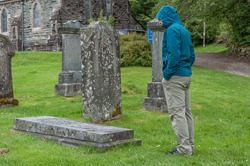 Man looking at a grave in ancient Scottish Balquhidder Parish church cemetery on a rainy day. Concept: visit to mysterious and evocative places in Scotland