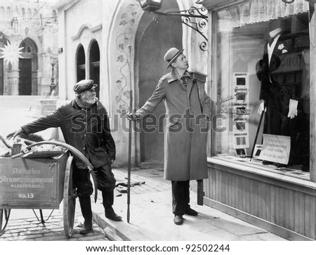 Man looking at a window display of a tuxedo
