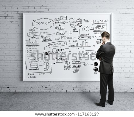 man looking at business strategy on board
