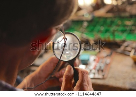 Man Looking At Circuit Board With Magnifying Glass                                - Shutterstock ID 1114644647