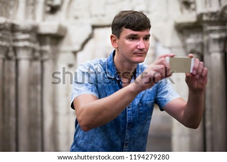 Man looking at exposition of antiquities and taking pictures on his phone in historical museum #1194279280