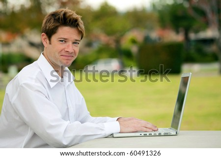 Man looking at his laptop outside