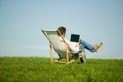 Man looking at laptop in field
