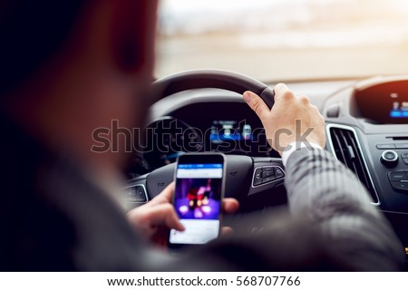 Man looking at mobile phone while driving a car.
