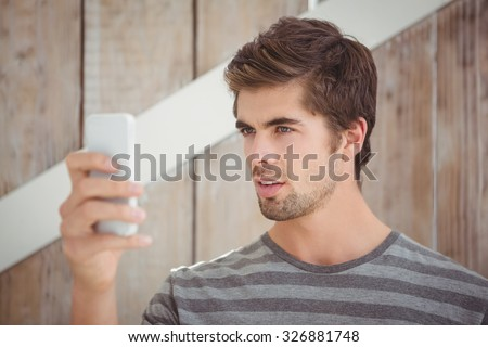 Man looking at mobile phone while standing against wooden wall