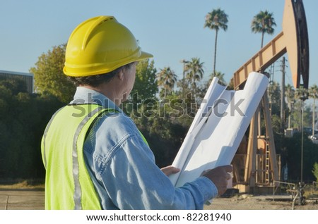 Man looking at oil pump/Oil Pump Inspector/Man in protective gear inspecting oil pump