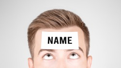 Man looking at paper with word Name pasted on his forehead