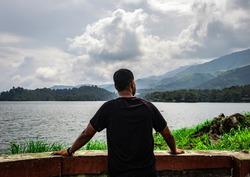 man looking at pristine lake with mountain background image is taken at banasura sagar dam wayanad kerala india. the natural beauty of this place is amazing.