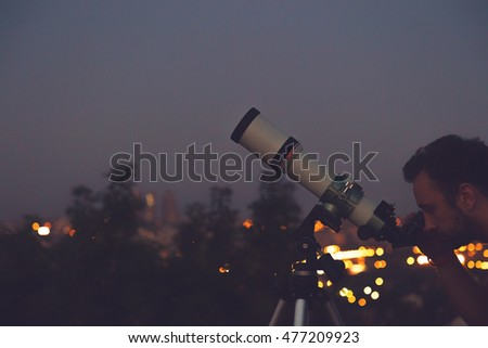 Man looking at the stars with telescope with de-focused city lights.