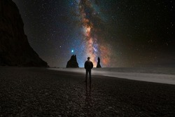 Man looking at the universe from the beach