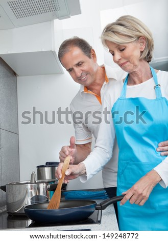 Man Looking At Woman Cooking Food In Kitchen