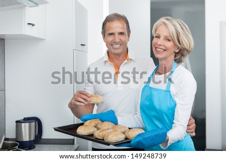 Man Looking At Woman Taking Baking Tray Out From Oven