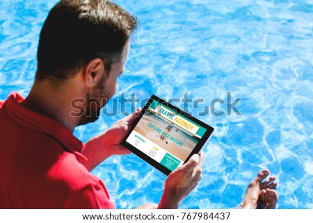 Man looking for travel destination in a travel agency website with a tablet, while sitting on the pool side. #767984437