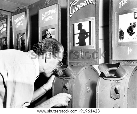 Man looking into a nickelodeon film machine
