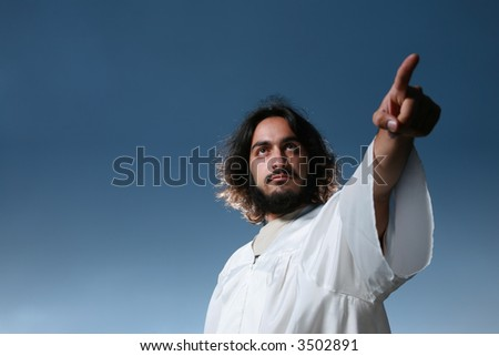 Man looking like Jesus pointing his finger, dramatic blue sky behind.
