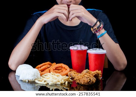 Man looking lots of junk fast food package
