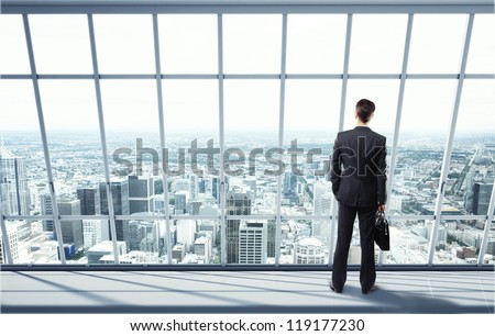 man looking on city through the window