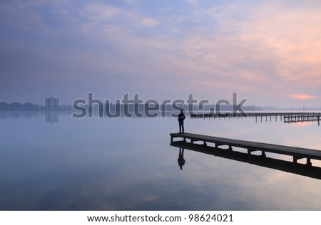 Man looking over a lake from a jetty during a cloudy sunrise.