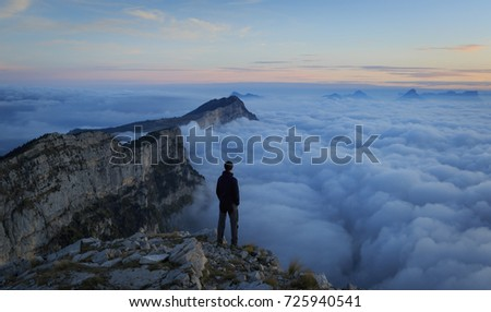 Man looking over a sea of clouds in the Vercors mountains. France.
