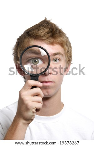 Man looking threw a magnifying glass in the studio
