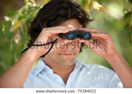 Man looking through a pair of binoculars