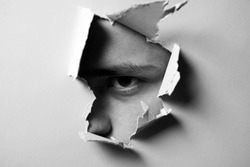 Man looking through paper. A jealous husband. Hole torn in paper with the eye of boy. Portrait of man looking through the hole in white paper. Distrustful look. Spy eye. Man's curiosity and gossip