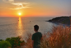 man looking to sunset on island Phuket Thailand for concept travel vacation and lonely