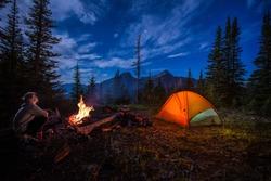 Man looking up at stars next to campfire and tent at night