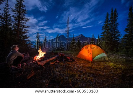 Man looking up at stars next to campfire and tent at night #603533180