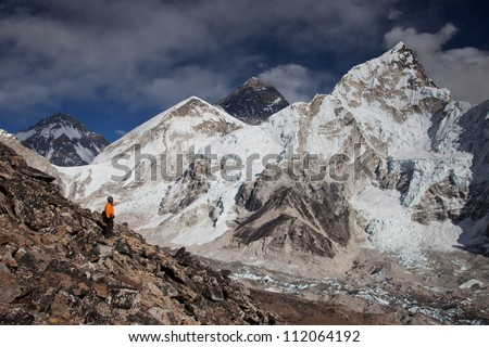 Man looking up to Himalayas and Mt Everest in Nepal while trekking.