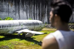 Man looks at abandoned plane in a quarry in Bali, Indonesia.