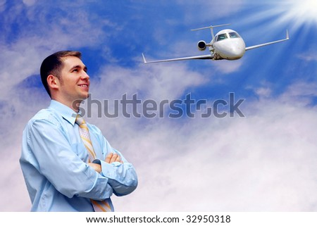 man looks at airplane in air on blue sky with sun