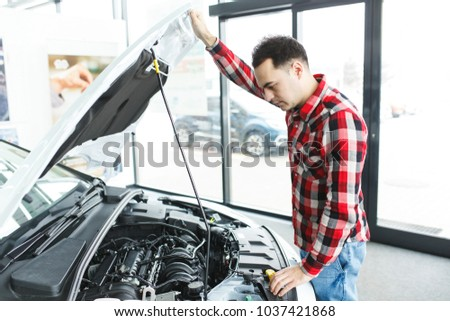 man looks at the motor in the car #1037421868