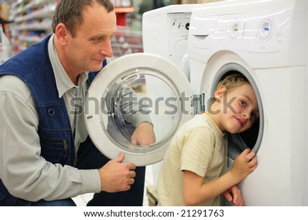 Man looks at washing machine in store, boy glances inward it
