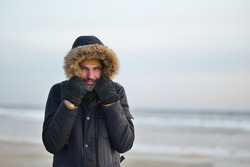 Man looks like shipster  in fur-hooded parka holds the hood because of the windy and cold weather at the  sand winter   beach
