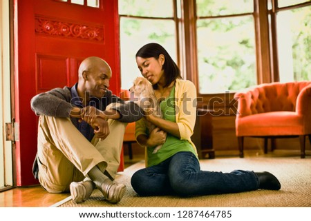 Man looks on as his partner cuddles a puppy while they sit on the floor of a living room.