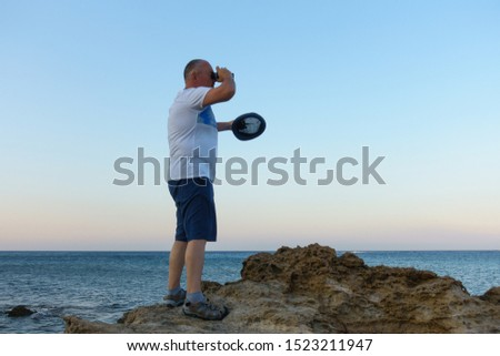 man looks through a telescope at the blue sea