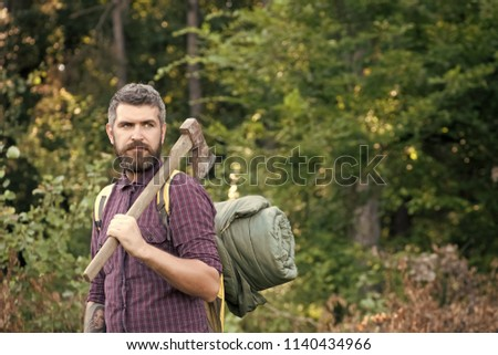 6aad192f453 Man lumberjack with bearded face hold backpack and axe on shoulder on  summer day on natural