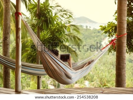 man lying in a hammock freelancer and running, beautiful mountain views, drinking wine