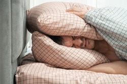 man lying in bed and covered with pillow. Insomnia, headache or depression or suffered concept