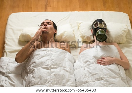 man lying in bed and smoking
