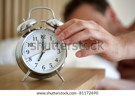 Man lying in bed turning off an alarm clock in the morning at 7am